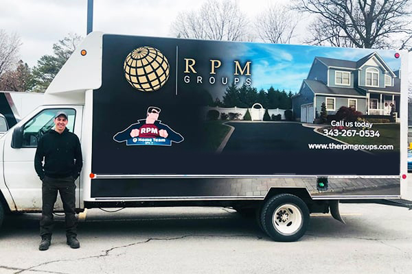 Proud RPM worker stands besides the RPM truck after a hard day of work